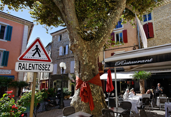 [FRANCE.PROVENCE 10883] 'Provence = slow down!'  Ralentissez orders this road sign on the Place aux Herbes in the town of Orange: slow down! To the relaxed pace of life in Provence. The orange bow, an idea of restaurant owner David of Les Amis, places the iconic platan in the centre of Provençal village life. Photo Paul Smit.