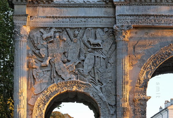 [FRANCE.PROVENCE 10905] 'Spoils of war in Orange.'  This relief on the Roman triumphal arch of Orange shows an unusual chaotic composition, not seen very often in classical art, since it likes order and symmetry. It is deliberate, as the image depicts a pile of shields, helmets daggers and other weapons of conquered Gauls.  Roman Orange was founded in 35 BC by veterans of the Second Augustan Legion and the reliefs on the arch celebrate two of their victories, one at sea and the other against the Gauls. Photo Paul Smit.