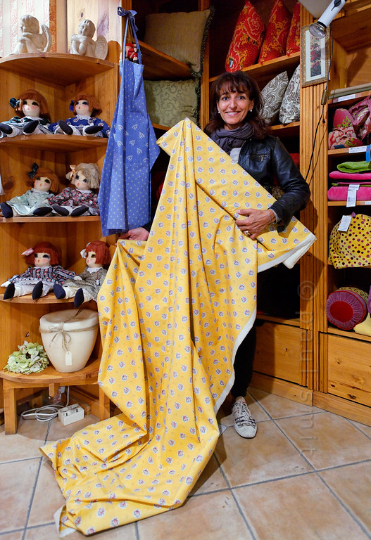[FRANCE.PROVENCE 10908] 'Provençal textiles.'  The town of Orange is located in Provence and besides colourful touristy textiles, it is still possible to find the more traditional Provençal fabrics, as here at Cosy (7 Place des Herbes) a yellow piece of fabric produced by the Provençal textiles company Olivades. This tradition originates in the 18th century textile industry of Orange that was initiated by Jean Rudolf Wetter. His factory, which employed more than five hundred workers in 1762, produced so-called Indiennes, printed textiles that were originally known from India. Orange's town museum preserves several specimens of Wetter's work. Photo Paul Smit.