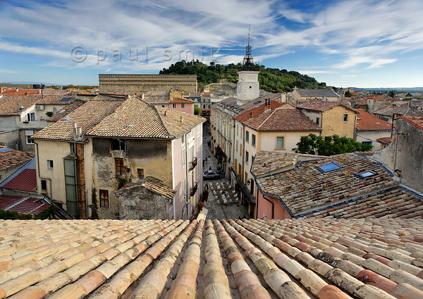 [FRANCE.PROVENCE 10876] 'Between cathedral and theatre.'  Orange is a small town with only 30.000 inhabitants. The old centre lies wedged between the enormous back wall of the Roman theatre and the cathedral, the roof of which provides the viewpoint for this picture. Between AD 1622 and 1673 the now wooded Hill of St.Eutrope, visible in the background, was crowned by one of the largest castles of Europe. It was built by the Dutch stadtholder Maurits, Prince of Orange, to defend the town and the freedom of religion it offered to French Protestants (Huguenots) who flocked to the town. Photo Paul Smit.
