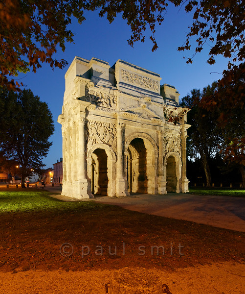 [FRANCE.PROVENCE 10903] 'Roman triumphal arch in Orange.'  The Roman triumphal arch of Orange is on the UNESCO World Heritage List, together with the town's Roman theatre. In 2009 a black layer of soot and dust was removed from the arch and now its white limestone looks as good as new. Roman Orange was founded in 35 BC by veterans of the Second Augustan Legion and the reliefs on the arch celebrate two of their victories, one at sea and the other against the Gauls. Photo Paul Smit.