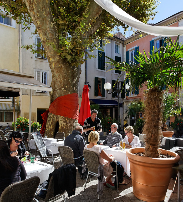[FRANCE.PROVENCE 10881] 'Orange bow.'  Platans are the iconic trees of Provence. That's why restaurant owner David of Les Amis has decorated the most delightful square of Orange - the Place aux Herbes - with a fancy bow. An orange one, of course. Photo Paul Smit.