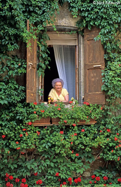[FRANCE.ALPSSOUTH 24.365] 'Old lady in Châtillon-1.'  	In the village of Châtillon-en-Diois an old lady proudly poses above her geraniums. Photo Mick Palarczyk.