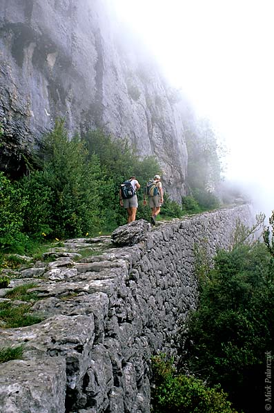 [FRANCE.ALPSNORTH 24.451] 'Hikers on mule track-1.'  South of Pont-en-Royans an ancient mule track leads up the perpendicular slope of the Grande Cournouse towards the Pas de l'Allier. Till the 19th century tracks like these were the only way to cross the Vercors in an east-west direction. They were mainly used by charcoal burners who worked high up in the woods. Photo Mick Palarczyk.