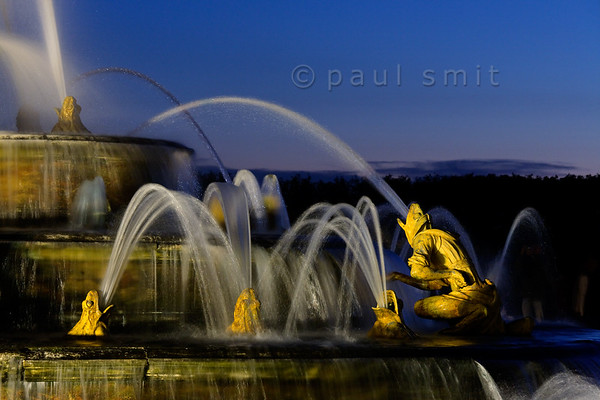 [FRANCE.ILEDEFRANCE 11096] 'Frogs at the Latona fountain, Palace Gardens, Versailles.'  During the Fountains Night Show (Grands Eaux Nocturnes) every single fountain comes to life in a balanced lighting. Inspired by Ovid's Metamorphoses, the Latona Fountain tells the story of Latona, mother of Apollo and Diana, protecting her children against the insults of the peasants of Lycia and calling on Jupiter to avenge them. He heard her plea and transformed them into frogs and lizards. The initial sculptures were made by Gaspard and Bathasar Marsy in 1670. The arrangement of the fountain was changed and finished by Jules Hardouin-Mansart in 1689. Photo Paul Smit.