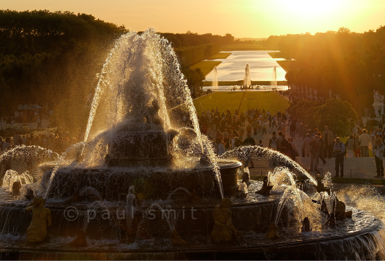 [FRANCE.ILEDEFRANCE 11083] 'Latona and Neptune fountains and Grand Canal, Versailles.'  The Latona and Neptune Fountains shining in the backlight of the sun setting behind the Grand Canal - it's the opening chord of the Fountains Night Show (Grands Eaux Nocturnes).  Inspired by Ovid's Metamorphoses, the fountain shows Latona (sculpted by Gaspard and Bathasar Marsy in 1670), mother of Apollo and Diana, protecting her children against the insults of the peasants of Lycia and calling on Jupiter to avenge them. He heard her plea and transformed them into frogs and lizards. The arrangement of the fountain was finished by Jules Hardouin-Mansart in 1689. Photo Paul Smit.