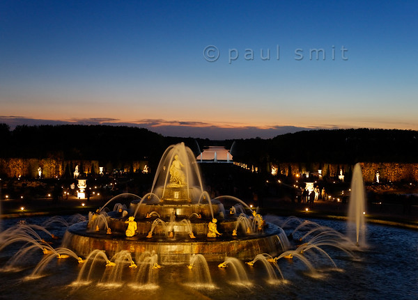 [FRANCE.ILEDEFRANCE 11093] 'Latona fountain during Fountains Night Show, Versailles.'  During the Fountains Night Show (Grands Eaux Nocturnes) every single fountain comes to life in a balanced lighting. The Grand Canal mirrors the sky in the background.  Inspired by Ovid's Metamorphoses, the fountain shows Latona (sculpted by Gaspard and Bathasar Marsy in 1670), mother of Apollo and Diana, protecting her children against the insults of the peasants of Lycia and calling on Jupiter to avenge them. He heard her plea and transformed them into frogs and lizards. The arrangement of the fountain was finished by Jules Hardouin-Mansart in 1689. Photo Paul Smit.