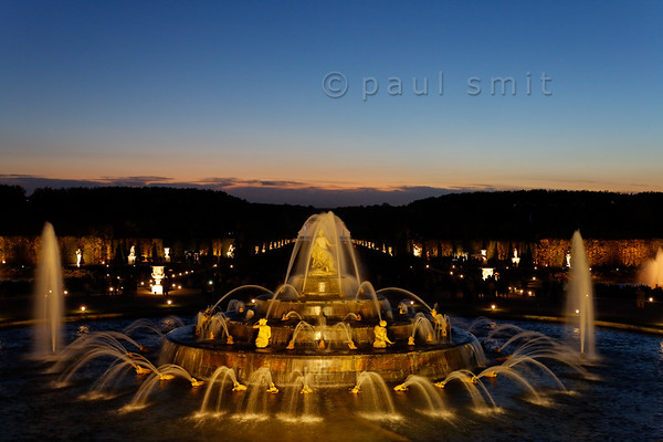 [FRANCE.ILEDEFRANCE 11094] 'Latona fountain during Fountains Night Show, Versailles.'  During the Fountains Night Show (Grands Eaux Nocturnes) every single fountain comes to life in a balanced lighting. Inspired by Ovid's Metamorphoses, the fountain shows Latona (sculpted by Gaspard and Bathasar Marsy in 1670), mother of Apollo and Diana, protecting her children against the insults of the peasants of Lycia and calling on Jupiter to avenge them. He heard her plea and transformed them into frogs and lizards. The arrangement of the fountain was finished by Jules Hardouin-Mansart in 1689. Photo Paul Smit.
