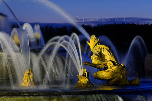 [FRANCE.ILEDEFRANCE 11095] 'Frogs at the Latona fountain, Palace Gardens, Versailles.'  During the Fountains Night Show (Grands Eaux Nocturnes) every single fountain comes to life in a balanced lighting. Inspired by Ovid's Metamorphoses, the Latona Fountain tells the story of Latona, mother of Apollo and Diana, protecting her children against the insults of the peasants of Lycia and calling on Jupiter to avenge them. He heard her plea and transformed them into frogs and lizards. The initial sculptures were made by Gaspard and Bathasar Marsy in 1670. The arrangement of the fountain was changed and finished by Jules Hardouin-Mansart in 1689. Photo Paul Smit.