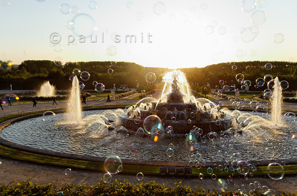 [FRANCE.ILEDEFRANCE 11078] 'Latona fountain, Palace Gardens, Versailles.'  Soap bubbles, the Latona Fountain shining in backlight, baroque music and a sunset in line with the Grand Canal - the Fountains Night Show (Grands Eaux Nocturnes) couldn't have a more fairy tale start.  Inspired by Ovid's Metamorphoses, the fountain shows Latona (sculpted by Gaspard and Bathasar Marsy in 1670), mother of Apollo and Diana, protecting her children against the insults of the peasants of Lycia and calling on Jupiter to avenge them. He heard her plea and transformed them into frogs and lizards. The arrangement of the fountain was finished by Jules Hardouin-Mansart in 1689. Photo Paul Smit.