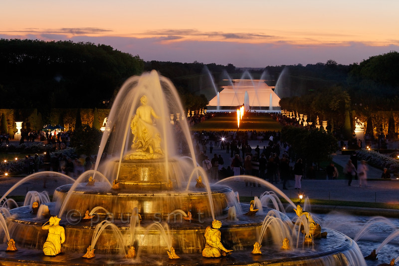 [FRANCE.ILEDEFRANCE 11092] 'Latona fountain during Fountains Night Show, Versailles.'  During the Fountains Night Show (Grands Eaux Nocturnes) every single fountain comes to life in a balanced lighting. The Grand Canal mirrors the sky in the background, while gas flames perform a ballet on baroque music.  Inspired by Ovid's Metamorphoses, the fountain shows Latona (sculpted by Gaspard and Bathasar Marsy in 1670), mother of Apollo and Diana, protecting her children against the insults of the peasants of Lycia and calling on Jupiter to avenge them. He heard her plea and transformed them into frogs and lizards. The arrangement of the fountain was finished by Jules Hardouin-Mansart in 1689. Photo Paul Smit.