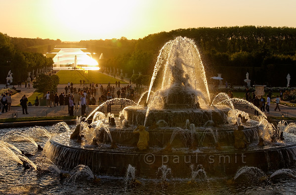 [FRANCE.ILEDEFRANCE 11081] 'Latona fountain and Grand Canal, Versailles.'  The Latona Fountain shining in the backlight of the sun setting behind the Grand Canal, while flames dance above the lawn - it's the opening chord of the Fountains Night Show (Grands Eaux Nocturnes).  Inspired by Ovid's Metamorphoses, the fountain shows Latona (sculpted by Gaspard and Bathasar Marsy in 1670), mother of Apollo and Diana, protecting her children against the insults of the peasants of Lycia and calling on Jupiter to avenge them. He heard her plea and transformed them into frogs and lizards. The arrangement of the fountain was finished by Jules Hardouin-Mansart in 1689. Photo Paul Smit.