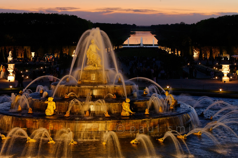 [FRANCE.ILEDEFRANCE 11091] 'Latona fountain during Fountains Night Show, Versailles.'  During the Fountains Night Show (Grands Eaux Nocturnes) every single fountain comes to life in a balanced lighting. The Grand Canal mirrors the sky in the background.  Inspired by Ovid's Metamorphoses, the fountain shows Latona (sculpted by Gaspard and Bathasar Marsy in 1670), mother of Apollo and Diana, protecting her children against the insults of the peasants of Lycia and calling on Jupiter to avenge them. He heard her plea and transformed them into frogs and lizards. The arrangement of the fountain was finished by Jules Hardouin-Mansart in 1689. Photo Paul Smit.