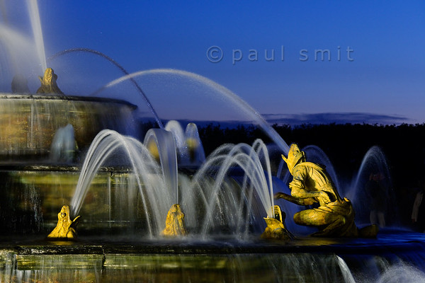 [FRANCE.ILEDEFRANCE 11097] 'Frogs at the Latona fountain, Palace Gardens, Versailles.'  During the Fountains Night Show (Grands Eaux Nocturnes) every single fountain comes to life in a balanced lighting. Inspired by Ovid's Metamorphoses, the Latona Fountain tells the story of Latona, mother of Apollo and Diana, protecting her children against the insults of the peasants of Lycia and calling on Jupiter to avenge them. He heard her plea and transformed them into frogs and lizards. The initial sculptures were made by Gaspard and Bathasar Marsy in 1670. The arrangement of the fountain was changed and finished by Jules Hardouin-Mansart in 1689. Photo Paul Smit.