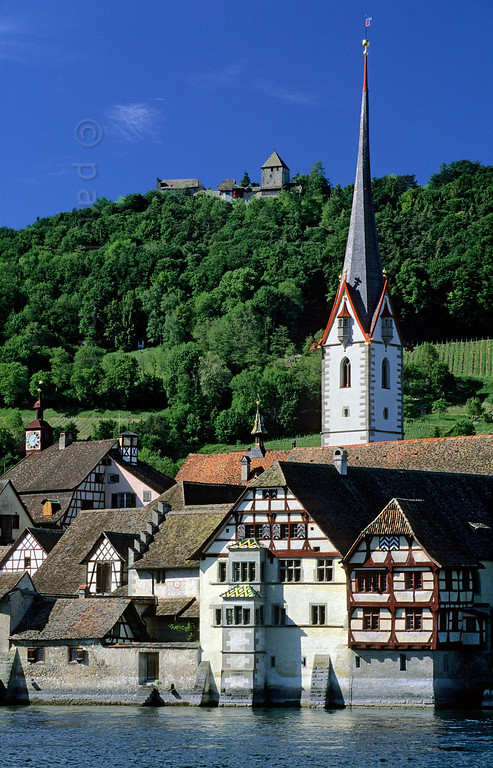 [SWITZER.MITTEL 00851] 'Stein am Rhein.'  The best view on Stein am Rhein is offered from the other side of the Rhine, with the timber framed abbey Sankt Georgen, the sleek church tower and castke Hohenklingen in the background. Photo Paul Smit.