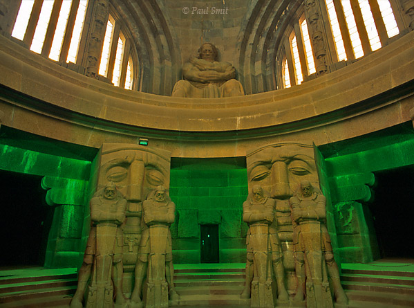 [GERMANY.SACHSEN 39]  'Völkerschlachtdenkmal near Leipzig.'  Everything looks heavy, the atmosphere is dark and the interior seems to be imported straight from the computer game Doom: the Völkerschlachtdenkmal. It seems as if the granite giants can wake up from their slumber any moment and crush you under their weight. It was built in 1913 as a monument for peace and commemorates the tens of thousands of deceased soldiers that fell one hundred years earlier in an enormous battle against Napoleon.  In reality nothing refers to peace, and everything to megalomanic, brainless Teutonhood. Maybe not so strange, being constructed only one year before the First World War. It shows clearly with which philosophy the country would thrust itself into war. Its Wagnerian, mythical Germanian kitsch makes clear that Germany was in fact ready for Nazism in 1913, ten years before its actual conception. Photo Paul Smit.