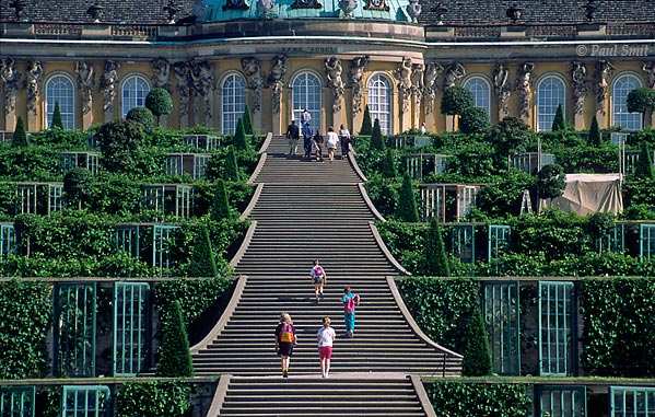[GERMANY.BRANDENBURG 11]  'Schloss and Park Sanssouci, Potsdam.'  Stairs climbing terraced vineyard garden towards the baroque Sanssouci palace, french for free of worries. This garden is the heart of the much larger, 290 ha Sanssouci Park, that itself is just the centerpiece of a whole chain of parks, gardens and palaces. Friedrich der Große (Frederick the Great) and generations of Prussian kings after him had these parks constructed along the banks of the Havel, a river that widens into an idyllic lake every few kilometers. The park landscape starts at Werder and reaches, via Potsdam, deep into Berlin. In the past the Glienicker Bridge, famous for its exchange of spies, divided this area. Since the German unification you can enjoy it as a whole and it has become a UNESCO World Heritage site. Photo Paul Smit.