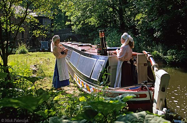 [BRITAIN.ENGMIDDLE 22.051] 'Narrow boat.'  The Caldon Canal is frequented by traditional narrow boats, like here at Froghall. Some boaters like to dress up in Victorian age fashion, as do these woman in 19th century boatwomen's clothes. Photo Mick Palarczyk.