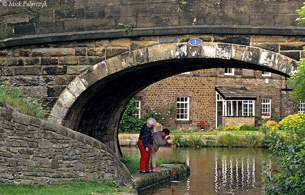 """[BRITAIN.ENGMIDDLE 22.156 'Fishing with a magnet.'  In Marple, at the junction of the Peak Forest Canal and the Macclesfield Canal, two women are having fun with a magnet on a string, trying to fish """"treasures"""" from the water. Photo Mick Palarczyk."""