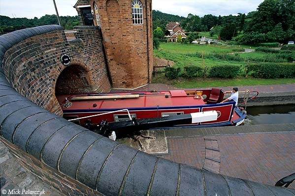 [BRITAIN.ENGMIDDLE 22.213 'Toll-cottage at Bratch.'  Near Wombourne, west of Birmingham, a boater on the Staffordshire & Worcester enters the Bratch lock which is overseen by an octagonal toll-cottage. Photo Mick Palarczyk.