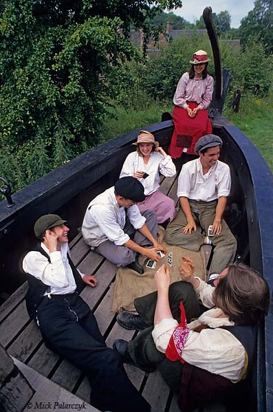 [BRITAIN.ENGMIDDLE 22.171 'Playing cards in icebreaker.'  Students in 19th century dress play a game of cards in an old wooden icebreaker, once used to keep open the canals in winter and now on display on the bank of the Shropshire Canal in Blists Hill Museum at Ironbridge. Photo Mick Palarczyk.