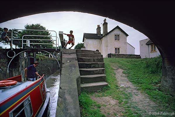 [BRITAIN.ENGMIDDLE 22.063 'Entering a lock.'  A son is holding open the lock gate while his father is entering the lock chamber at Hazlehurst Junction (near leek) on the Caldon Canal. Photo Mick Palarczyk.