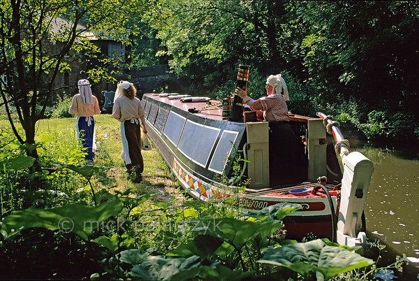 [BRITAIN.MIDDLEENGLAND 22050] 'Narrow boat.'  The Caldon Canal is frequented by traditional narrow boats, like here at Froghall. Some boaters like to dress up in Victorian age fashion, as do these woman in 19th century boatwomen's clothes. The lady at right is removing the chimney of the onboard kitchen after dinner. Photo Mick Palarczyk.