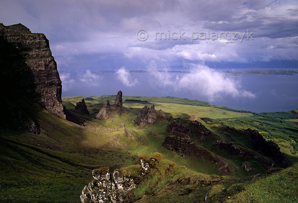 """[BRITAIN.HEBRIDES 27759] 'The Storr seen from the south.'  The Storr (left) is the the highest point of the Trotternish Ridge, a steep escarpment that forms the backbone of Skye's Trotternish Peninsula. The Ridge consists of lava sheets that welled up from the earth as The Atlantic Ocean opened up and Western Europe and America started to drift apart 60 millions years ago. Parts of the escarpment have tumbled down in massive landslides, leaving jumble of rocks  and peaks at the foot of the Storr, the highest of which is called the """"Old Man""""."""