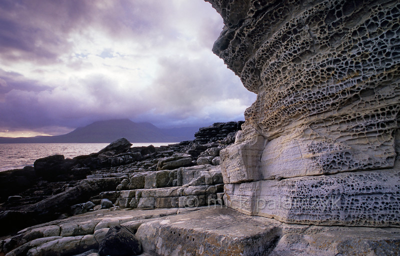 [BRITAIN.HEBRIDES 27837] 'Holy Cliffs at Elgol.'  The Skye coast near Elgol offers views across Loch Scavaig with the Cuillins on the northern horizon. The 'Holy Cliffs', seen here in the foreground, consist of Jurassic sandstone. Its quartz grains are cemented together by chalk particles, as a result of which they have 'weathered-out' in an irregular manner to give a curious 'honeycomb' effect. Photo Mick Palarczyk.