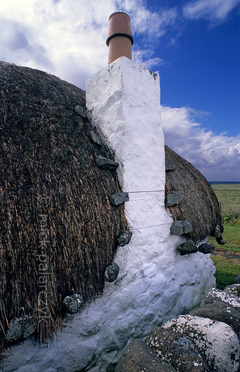 [BRITAIN.HEBRIDES 27773] 'Cottage in Bornesketaig.'  In the northwest of Skye's Trotternish Peninsula, Beaton's  Crofthouse in Bornesketaig has the straw of its roofs protected from wind damage by netting that is held in place by anker stones. Photo Mick Palarczyk.