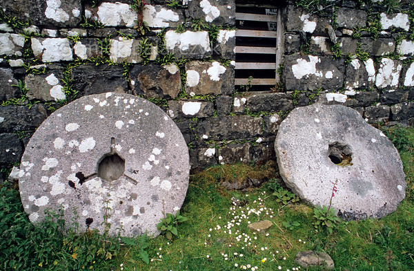 [BRITAIN.HEBRIDES 27823] 'Mill stones at Glendale.'  	Two old liched covered mill stones rest against the outer wall of the Glendale watermill which is situated at a bay on the west coast of Skye. Crofters once brought their grain by sea, some from as far away as the Outer Hebrides. Photo Mick Palarczyk.