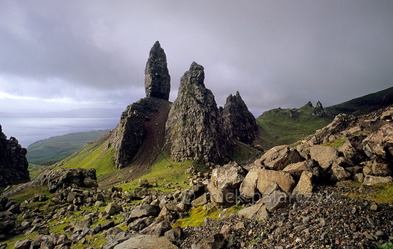 [BRITAIN.HEBRIDES 27764] 'The Old Man of Storr seen from the north.'  On Skye's Trotternish Peninsula the pinnacle of the Old Man of Storr gives a dramatic touch to the landscape. Its geological history is no less dramatic. As most of northern Skye, the Old Man consists of lava that welled up from the earth as The Atlantic Ocean opened up and Western Europe and America started to drift apart 60 millions years ago. On the eastern edge of the Trotternish peninsula parts of the formed lava sheet tumbled down in massive landslides, creating jagged peaks such as the Old Man. Photo Mick Palarczyk.