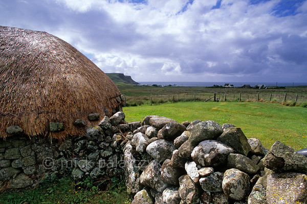 [BRITAIN.HEBRIDES 27776] 'Barn in Bornesketaig.'  In the northwest of Skye's Trotternish Peninsula the barn of Beaton's Crofthouse in Bornesketaig has the straw of its roofs protected from wind damage by netting that is held in place by anker stones. Photo Mick Palarczyk.