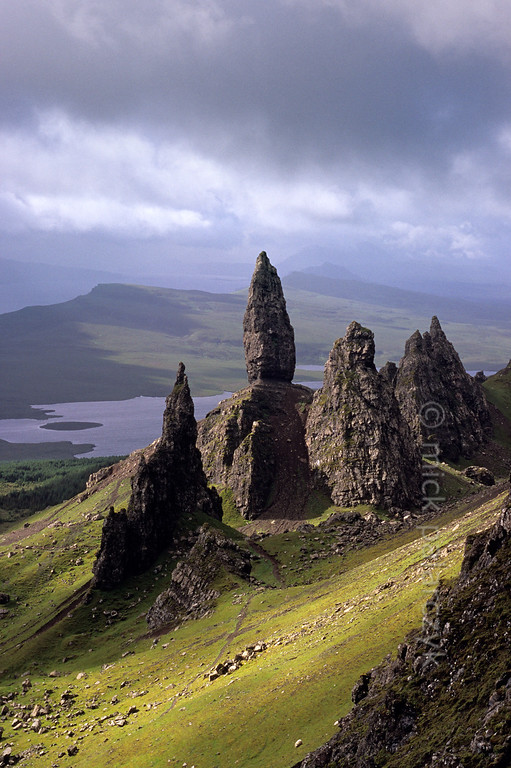 [BRITAIN.HEBRIDES 27752] 'The Old Man of Storr seen from the Trotternish Ridge.'  	On Skye's Trotternish Peninsula the pinnacle of the Old Man of Storr gives a dramatic touch to the landscape. Its geological history is no less dramatic. As most of northern Skye, the Old Man consists of lava that welled up from the earth as The Atlantic Ocean opened up and Western Europe and America started to drift apart 60 millions years ago. On the eastern edge of the Trotternish peninsula parts of the formed lava sheet tumbled down in massive landslides, creating jagged peaks such as the Old Man. Photo Mick Palarczyk.