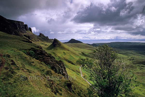 [BRITAIN.HEBRIDES 27801] 'Quiraing.'  	On Skye's Trotternish Peninsula the steep escarpment of the Quiraing offers some of the island's most dramatic landscapes. The hillocks and pinnacles at the foot of the ridge are the result of massive landslides in which layers of basalt lava's slumped down from the top of the escarpment over older relatively weak sedimentary rocks. Photo Mick Palarczyk.