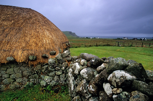[BRITAIN.HEBRIDES 27775] 'Barn in Bornesketaig.'  In the northwest of Skye's Trotternish Peninsula the barn of Beaton's Crofthouse in Bornesketaig has the straw of its roofs protected from wind damage by netting that is held in place by anker stones. Photo Mick Palarczyk.
