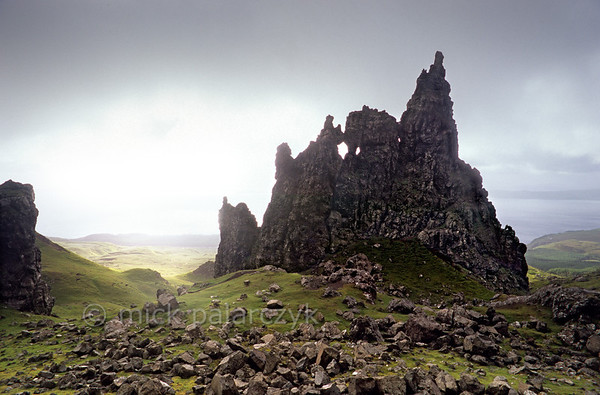 "[BRITAIN.HEBRIDES 27769] 'The Cathedral.'  	On Skye's Trotternish Peninsula the basalt pinnacles at the foot of the Storr give a dramatic touch to the landscape. This rock formation is called ""The Cathedral"" for obvious reasons. In the distance the Sound of Raasay can be seen. Photo Mick Palarczyk."