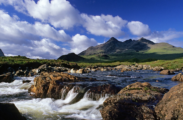 [BRITAIN.HEBRIDES 27833] 'Sligachan River and Cuillins.'  	Skye's Cuillins are considered the most impressive mountain range in the British Isles and a mecca for hikers and climbers. They are the remnants of large volcanoes which erupted when the Atlantic Ocean opened up and the American continent started  to drift away from Europe, 60 million years ago. The foreground of the picture shows the Sligachan River. Photo Mick Palarczyk.