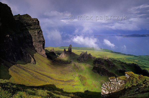 """[BRITAIN.HEBRIDES 27757] 'The Storr seen from the south.'  The Storr (left) is the the highest point of the Trotternish Ridge, a steep escarpment that forms the backbone of Skye's Trotternish Peninsula. The Ridge consists of lava sheets that welled up from the earth as The Atlantic Ocean opened up and Western Europe and America started to drift apart 60 millions years ago. Parts of the escarpment have tumbled down in massive landslides, leaving jumble of rocks  and peaks at the foot of the Storr, the highest of which is called the """"Old Man"""". Photo Mick Palarczyk."""