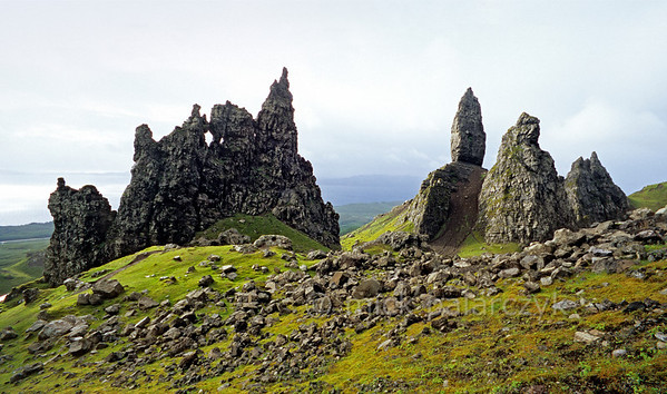 """[BRITAIN.HEBRIDES 27767] 'The Cathedral and The Old Man.'  On Skye's Trotternish Peninsula the basalt pinnacles at the foot of the Storr give a dramatic touch to the landscape. To the left is a rock formation called """"The Cathedral"""" for obvious reasons. The peak to the right which seems to be standing on a socle is called """"The Old Man"""". In the distance the Sound of Raasay can be seen. Photo Mick Palarczyk."""