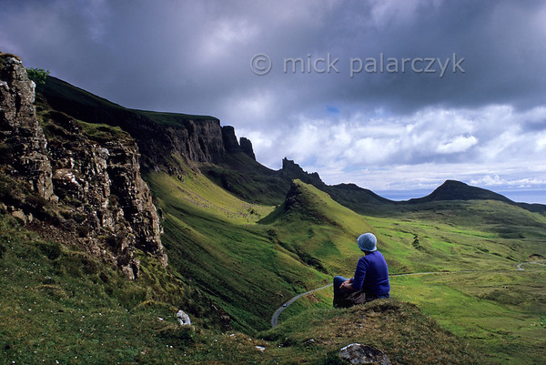 [BRITAIN.HEBRIDES 27798] 'Quiraing.'  	On Skye's Trotternish Peninsula the steep escarpment of the Quiraing offers some of the island's most dramatic landscapes. The hillocks and pinnacles at the foot of the ridge are the result of massive landslides in which layers of basalt lava's slumped down from the top of the escarpment over older relatively weak sedimentary rocks. Photo Mick Palarczyk.