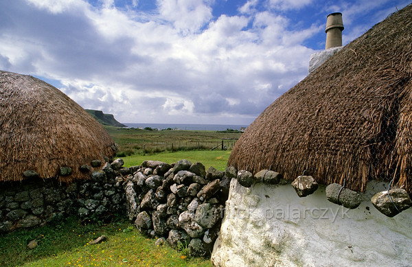 [BRITAIN.HEBRIDES 27771] 'Cottage and barn in Bornesketaig.'  In the northwest of Skye's Trotternish Peninsula, Beaton's  Crofthouse in Bornesketaig has the straw of its roofs protected from wind damage by netting that is held in place by anker stones. Photo Mick Palarczyk.