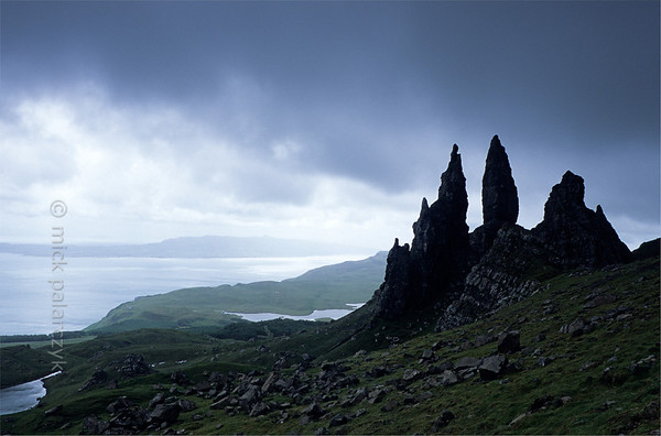 [BRITAIN.HEBRIDES 27761] 'The Old Man of Storr seen from the north.'  	On Skye's Trotternish Peninsula the pinnacle of the Old Man of Storr gives a dramatic touch to the landscape. Its geological history is no less dramatic. As most of northern Skye, the Old Man consists of lava that welled up from the earth as The Atlantic Ocean opened up and Western Europe and America started to drift apart 60 millions years ago. On the eastern edge of the Trotternish peninsula parts of the formed lava sheet tumbled down in massive landslides, creating jagged peaks such as the Old Man. Photo Mick Palarczyk.