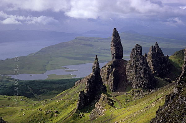 [BRITAIN.HEBRIDES 27755] 'The Old Man of Storr seen from the Trotternish Ridge.'  On Skye's Trotternish Peninsula the pinnacle of the Old Man of Storr gives a dramatic touch to the landscape. Its geological history is no less dramatic. As most of northern Skye, the Old Man consists of lava that welled up from the earth as The Atlantic Ocean opened up and Western Europe and America started to drift apart 60 millions years ago. On the eastern edge of the Trotternish peninsula parts of the formed lava sheet tumbled down in massive landslides, creating jagged peaks such as the Old Man. Photo Mick Palarczyk.