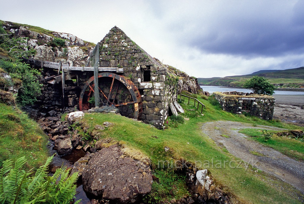 [BRITAIN.HEBRIDES 27818] 'Glendale watermill.'  Glendale watermill is situated at a bay on the west coast of Skye. Via a wooden gutter a small brook delivers its water on the upper part of the iron (overshot) wheel. Crofters once brought their grain by sea, some from as far away as the Outer Hebrides. They even brought their own supply of peat which was used in the drying kiln (the now roofless building on the right) to reduce the moisture content of the grain prior to grinding. Photo Mick Palarczyk.