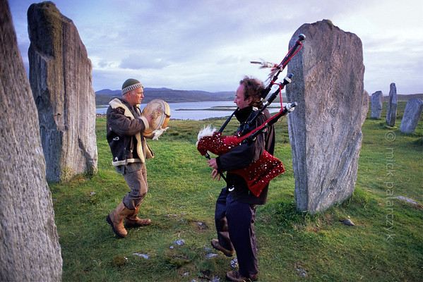 [BRITAIN.HEBRIDES 27673] 'Piping at Callanish stone circle.'  On a summer evening local musicians are enhancing the mystic atmosphere of the neolithic stone circle at Callanish on the Isle of Lewis. The circle was constructed around 2700 BC on the shore of East Loch Roag, an estuary along the north coast of Lewis. Photo Mick Palarczyk.