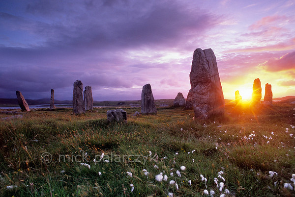 [BRITAIN.HEBRIDES 27685] 'Sunset at Callanish III'  	On the shore of East Loch Roag, an estuary along the north coast of Lewis, you can find several neolithic stone circles. This one, surrounded by the white plumes of common cottongrass is called Callanish III. It is less spectacular than the better known primary circle at Callanish I, but still offers a mystic experience during sunset. Photo Mick Palarczyk.