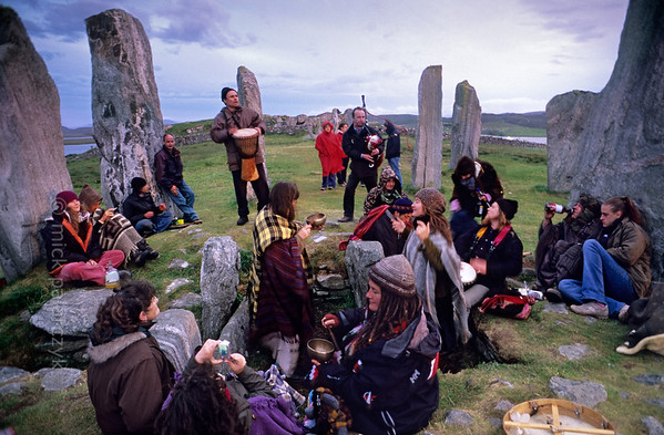 """[BRITAIN.HEBRIDES 27678] 'Celebrating the summer solstice.'  On the Isle of Lewis the neolithic stone circle at Callanish has been called """"Scotland's Stonehenge"""". Just as its English counterpart, on the evening of june 21th it receives a variety people who want to celebrate the summer solstice. On the foreground people are sitting and dancing in the burial chamber that occupies the center of the stone circle. Photo Mick Palarczyk."""
