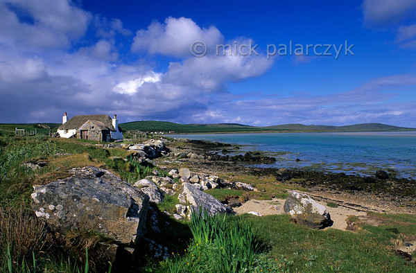 [BRITAIN.HEBRIDES 27737] 'Cottage on North Uist.'  Near Malacleit a thatched cottage overlooks a bay on the northern coast of the Isle of North Uist. Photo Mick Palarczyk.