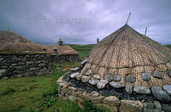 [BRITAIN.HEBRIDES 27711] 'Thatched roofs in Gearrannan village.'  	These thatched roofs in Gearrannan are protected against wind damage by netting and ropes held in place by anker stones. The village of Gearrannan is located at a small bay on the northern coast of the Isle of Lewis. The last ageing residents left the 17th century village in the 1970s. It has now been lovingly restored and houses a youth hostel, self-catering accommodation and a museum. Photo Mick Palarczyk.